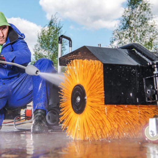 Men Cleaning His Power Brush Using Pressure Washer.